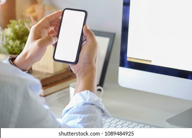 Business man holding smart phone on desk work in office.