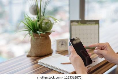 Business man holding smartphone to update calendar with notebook pencil diary vase on table with blurred calendar. planning scheduling agenda and event for 2018. Calendar and Planning concept.