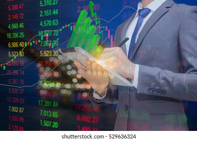 Business man holding tablet with green stick graph on top and background is oil and gas processing platform and stock index graph with indicator, Oil and gas investment concept.