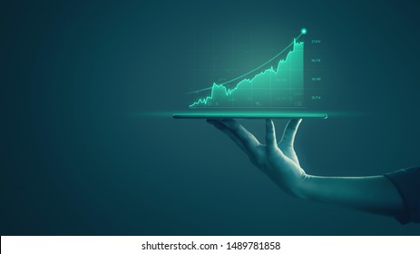 Business man holding tablet and showing holographic graphs and stock market statistics gain profits. Concept of growth planning and business strategy. Display of good economy form digital screen.