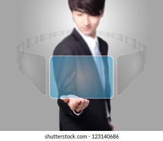 Business man holding a touch screen ( choosing from many virtual screen ) with empty copy space on gray background, asian model