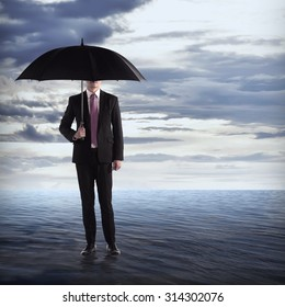 Business man holding umbrella in the middle of the ocean