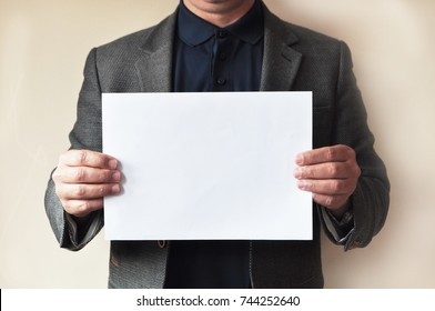 A business man holding a white sheet of paper - your text here