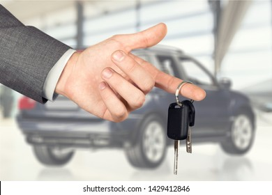 A business man holds car key on car background