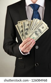 Business man holds lot of money on grey background