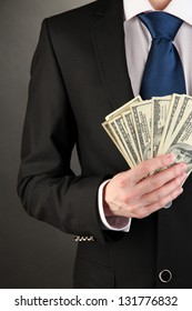 Business man holds lot of money on black background