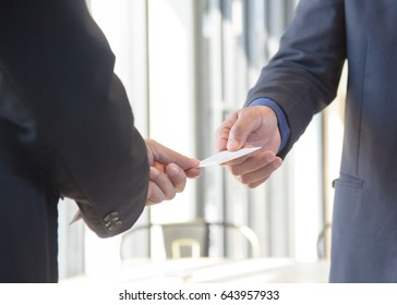 business man introducing himself and showing his name card to partner.