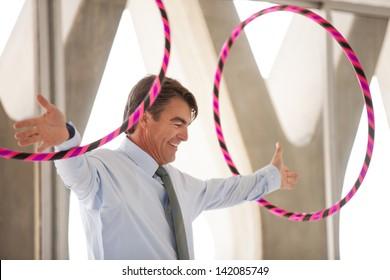 Business man jumping through hoops metaphorically