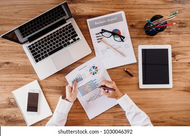 Business man with laptop computer and document report. Young bearded businessman is sitting in office at table,working and drinking coffee.On table is laptop and tablet computer with graphs