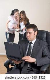 business man with laptop leading a team in an office environment