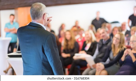 Business man leading a business workshop. Corporate executive delivering a presentation to his colleagues during meeting or in-house business training. Business and entrepreneurship concept.