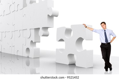 business man leaning on a puzzle piece - good concept for business solutions isolated over a white background