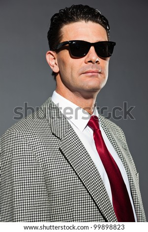b74eaeda8cb9 Business man with light grey suit and red tie isolated on dark background.  Wearing black sunglasses. Studio shot. - Image