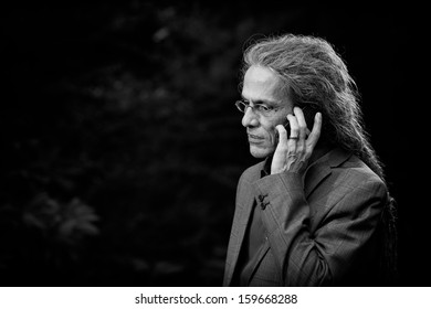 Business man with long dreadlocks working calling with a smartphone against a dark background with trees, providing for negative space