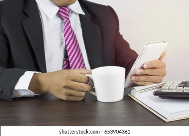 business man look information,  use phone and  drink cup of coffee in work place