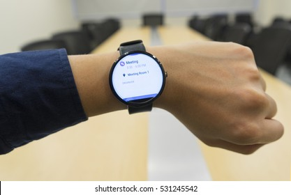 business man look smartwatch Leather watchbands black color circle front on left hand at meeting room show agenda schedule when where and organizer