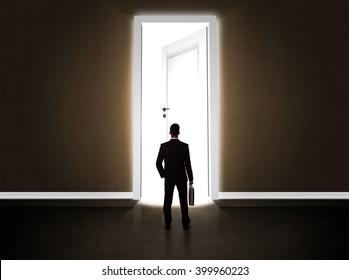 Business man looking at big bright opened door concept