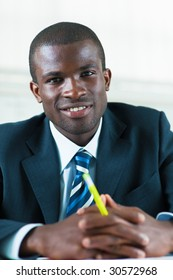 business man looking at camera with hands clasped