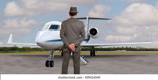 Business man looking at his private airplane wearing a hat