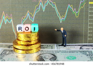 "A business man is looking to his profit from investment. conceptual image for the word ""Return On Investment"" (ROI)."