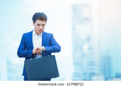 Business man looking his watch and holding business bag while standing at the street business tower in the background