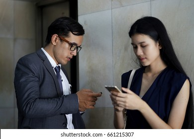 Business man looking at the mobile phone and working woman looking to her smart phone. Social Ignored or phubbing