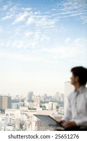 Business man looking at Tokyo skyline with laptop