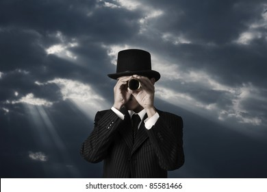business man looks through a telescope in darkness