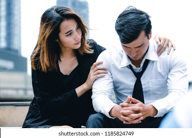 Business man lost job, lost in depression sitting on the subway stair suffering emotional pain with colleague comfort near by. Man sad,unhappy, problem at work. Woman comfort unhappy young man.
