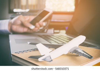 Business man is making call in office for global communication. A man holding mobile phone with Airplane on for ground for Business travel communication concept.