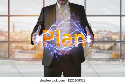 Business man making electricity light word plan from his hands concept