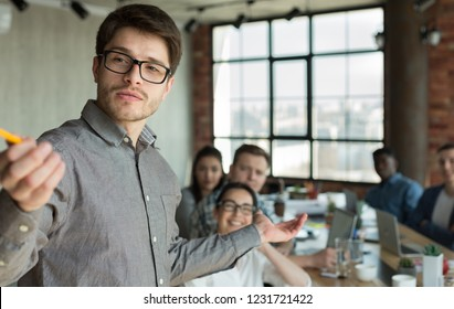 Business man making presentation to colleagues at office during meeting or workshop. Businessman point at camera like flipboard, copy space