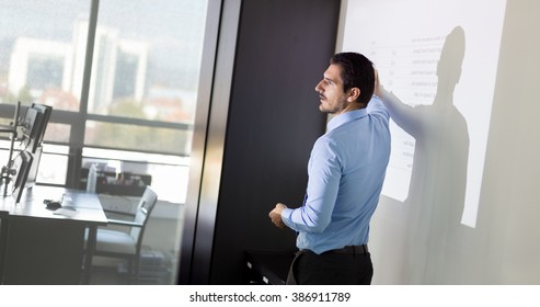 Business man making a presentation in front of whiteboard. Business executive delivering a presentation to his colleagues during meeting or in-house business training.