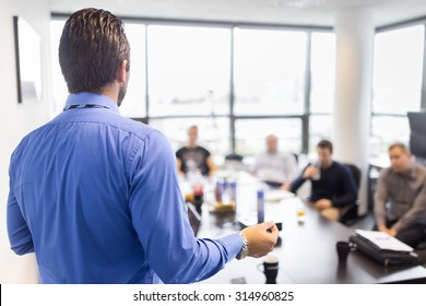 Business man making a presentation at office. Business executive delivering a presentation to his colleagues during meeting or in-house business training, explaining business plans to his employees.