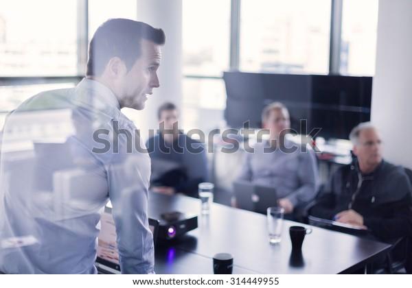 Geschäftsmann, der sich im Büro präsentiert. Geschäftsführer, der seinen Kollegen während des Meetings oder der betriebsinternen Schulung eine Präsentation übergab und seinen Mitarbeitern Geschäftspläne erläutert.