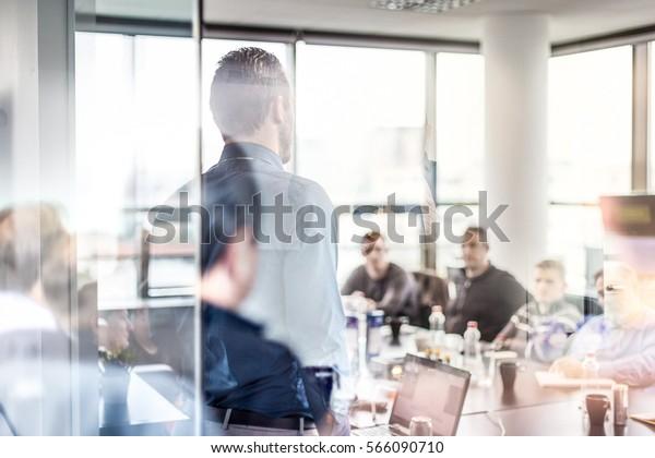 会社でプレゼンをする実業家。会議または社内ワークショップで、同僚にプレゼンテーションを行うビジネスエグゼクティブ。背面図。ビジネスと起業家精神。