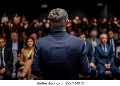 Business man is making a speech in front of a big audience at a conference hall. Speaker giving a talk on corporate business or political conference. Politician talking to group of people