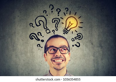 Business man with many questions and solution light bulb above head