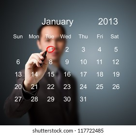business man marking new year day on January 2013 calendar