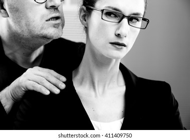 business man maybe a manager molesting a woman on the job in their workplace