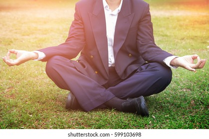 Business man meditation relaxing in a park. Close up. relax time and reduce stress at work.