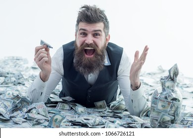 Business man, millionaire, billionaire, bearded man with many banknote. Business man lying in banknotes. Bearded man holds plane from bankote. Bank advertising. Travels.