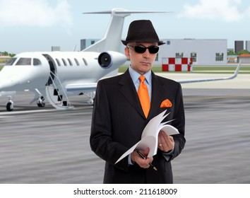 Business man next to a private jet looking at documents