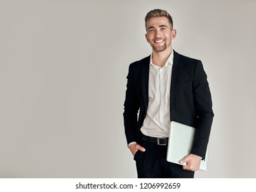 Business man with notebook isolated. Business man holding laptop computer and smiling