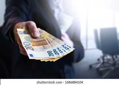 Business man in office holding european Euro bills. Money against coronavirus fight with global economical crises.