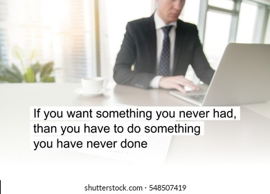 """Business man in office. Photo with motivational text """"If you want something you never had, than you have to do something you have never done"""""""