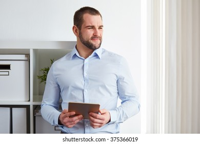 Business man in office with tablet computer, looking out the window