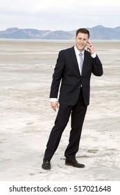 Business man on cell phone at the salt lake city salt flats