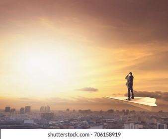 business man on paper plane spying by binocular to urban scene