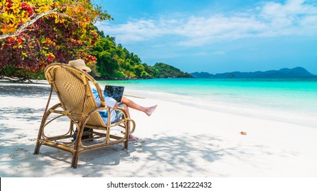 Business man on summer vacation trip, Traveler man relaxing on beautiful natural white sand beach using laptop, Andaman sea beach, Tourism destination Asia, Tourist holiday outdoor travel concept
